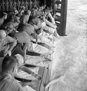 Burial at sea for the officers and men of the USS Intrepid (CV-11) who lost their lives when the carrier was hit by Japanese bombs during operations in the Philippines. Photo courtesy of the Naval Photographic Center of the National Archives.