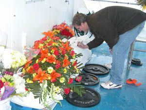 A guest at a sea burial signs a shroud before it is placed in the ocean. Photo courtesy of New England Burials at Sea
