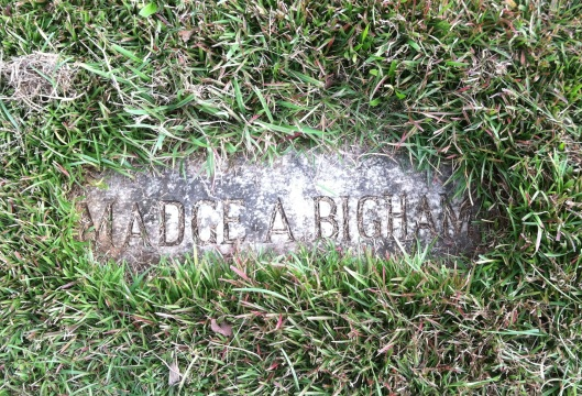 "Madge Bigham's simple, flat grave marker lay hidden under grass and dirt until I found it. Since this photo was taken, it's been ""weed whacked"" and looks much better."