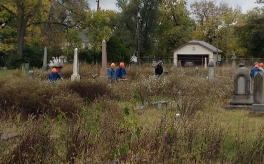 Workers dive into the jungle of weeds and other brush at Old Greenwood Cemetery. Photo courtesy of WHIO