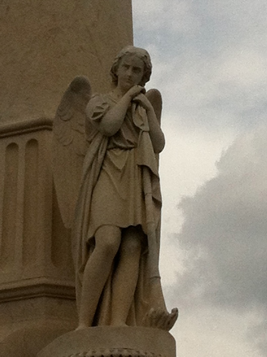 An angel leans against his trumpet at the base of the monument.
