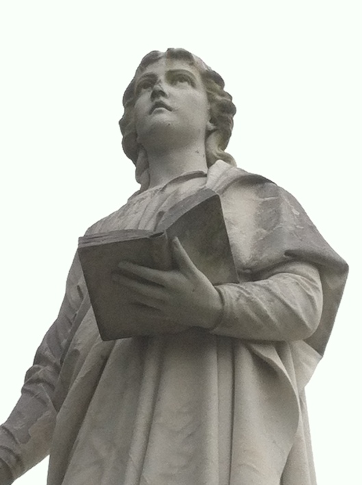 The sculpture of St. John the Baptist against the plain white sky gives it a stark, bare look.