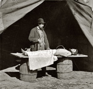 Dr. Richard Burr, an embalming surgeon in Frederick, Va. He is shown embalming a soldier recovered from the battlefield. You can see the embalming pump in his right hand, and the tubing attached to it above the chest of the soldier's body. Embalming tables were not usually available in the field, so he used a door placed over two large barrels.