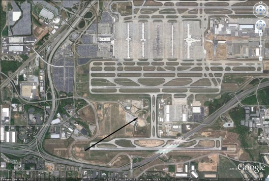 This areal view of the airport runways shows the location of both cemeteries, the black arrow runs between them.