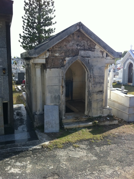 """This is a personal family mausoleum.  The upper, ground level portion was originally meant to be a small chapel and would have had an altar just inside the door.  A marble slab would be removed in the floor to access the family crypt where several coffins would reside depending on the size of the structure and the crypt. This one has long been abandoned. Perhaps the family not able to keep up the cost of the burial plot and building?  Maybe it was desecrated by others. I don't know, but it certainly conjures a story. You can see the crypt is open and was empty when I peered in.  Very, very eerie. """