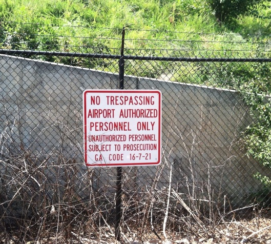 This sign reminds you that you are only a handful of yards from a gigantic runway.