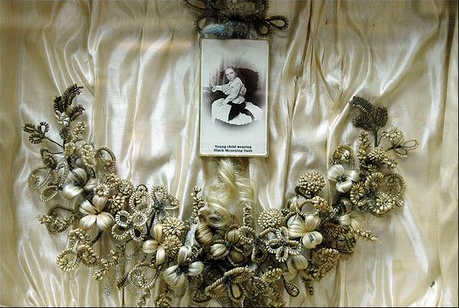 This shadow box with a picture of a girl in mourning is lined with material usually reserved for a coffin. The wreath is made with hair from the girl and the girl's mother, who had died. Photo by Richard Gwinn.