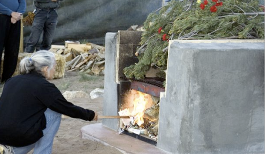 A woman adds wood to the fire beneath Crestone's pyre during a funeral service. Photo courtesy of U.S. Funerals Online.