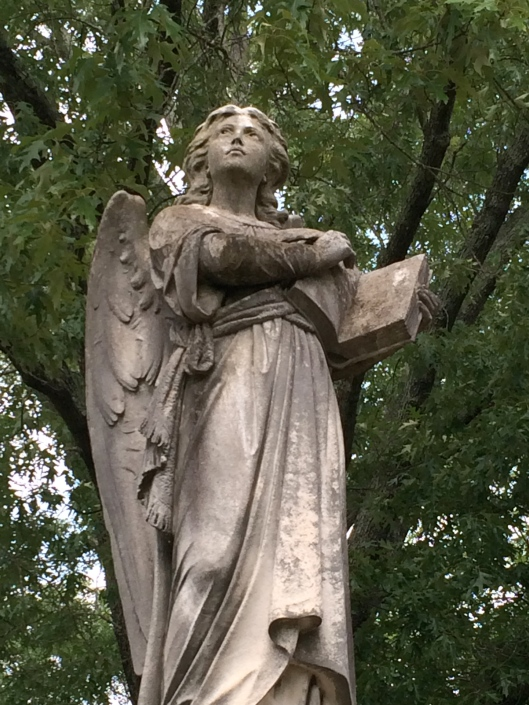 Holding what looks to be an open Bible, this angel has an almost defiant look on her face as she gazes Heavenward.