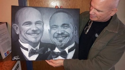 A pleased client shows off the portrait of his late partner painted with traces of his ashes. Photo courtesy of Adam Brown's website Adam Brown's Gallery.