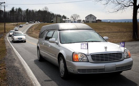 "This is a picture of the funeral procession for seven children in Pennsylvania who died in a house first. The purple and white flags marked ""funeral"" are typically used by most funeral homes or they ask drivers to simply turn on their headlights. Photo courtesy of The Patriot News."