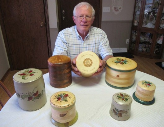Tom Caflisch of River Falls, Wisc. holds a wooden urn his remains will be placed in someday. A Navy veteran, he etched the dates of his military service on the lid. In his part-time urn business, he personalizes cremation urns for customers who want their military service or other identification noted on their burial urns. Photo courtesy of Meg Jones/Milwaukee Journal Sentinel.