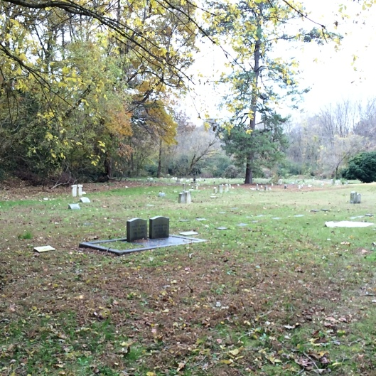 To the left of the entrance, you can see the older, disorganized section of the cemetery. Some of the graves are sunk so deep you cannot read the markers.