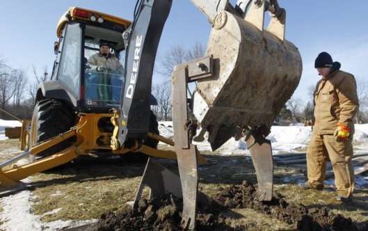 "Cory Lidwin (left) and Rick Budnick use ""frost teeth"" attached to a backhoe while digging a grave Monday at Highland Memorial Park Cemetery in New Berlin, Wisc. This enables them to penetrate the frost line of the soil. Photo by Mark Hoffman, Milwaukee Wisconsin Journal Sentinel."