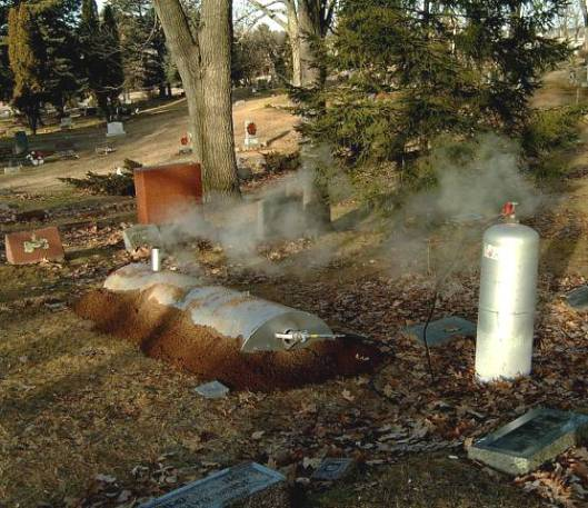 This is an example of a more primitive grave thawer that resembles an oil barrel. Propane is used to heat the barrel which in turns, thaws the ground to make it diggable.