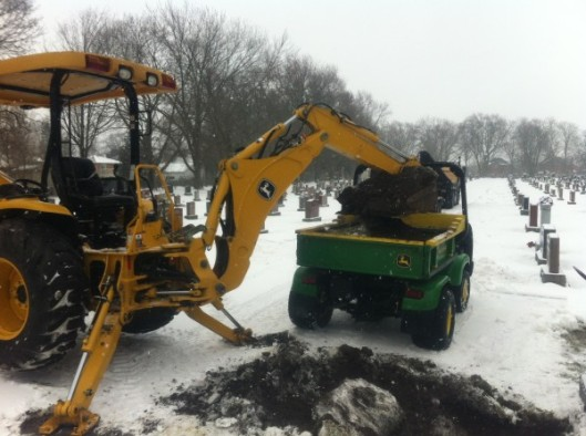 P.D. Baker Ltd. in Ontario, Canada uses a John Deere 110 TLB (tractor/loader/backhoe) and Pro-Gator. Both machines maneuver through tight cemetery spaces easily, and the lightweight turf tires on both distribute weight to minimize damage to cemetery grounds and flower beds. Photo courtesy of P.D. Baker Ltd.