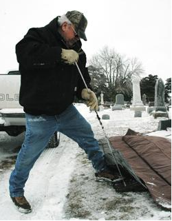 Graceland Cemetery Superintendent Bruce Hodge uses a ground thawing blanket, powered by a generator, to soften the frozen soil to dig a grave. Photo courtesy of the Creston News Advertiser.