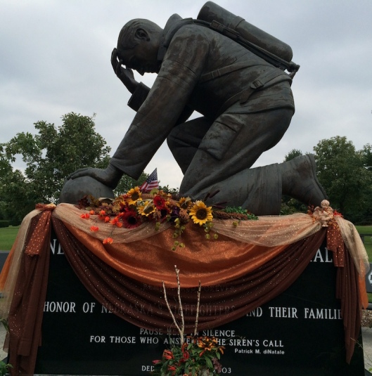The centerpiece of the display is a large bronze figure of a kneeling firefighter, sculpted by S. Mariami in 2001 and dedicated in 2003.