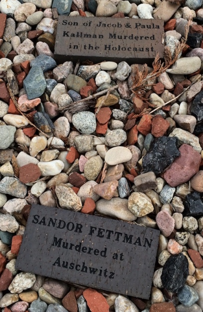 Plaques bearing the names of Holocaust victims are nestled amid the gravel that surrounds the sculpture.