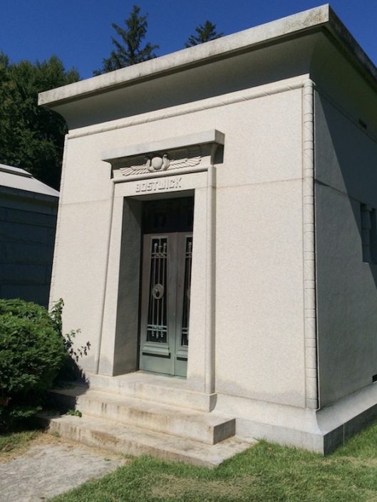 The Bostwick mausoleum features Egyptian motifs such as the winged disc and cobras.