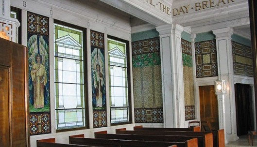 The windows are treated in an architectural scheme of classic detail to give abundant light to the interior and enhance the rich wall decor. The highlight of which is the four angel figures on the transept wall, created by J & R Lamb of New York. Photo source: Forest Lawn Memorial Park web site.