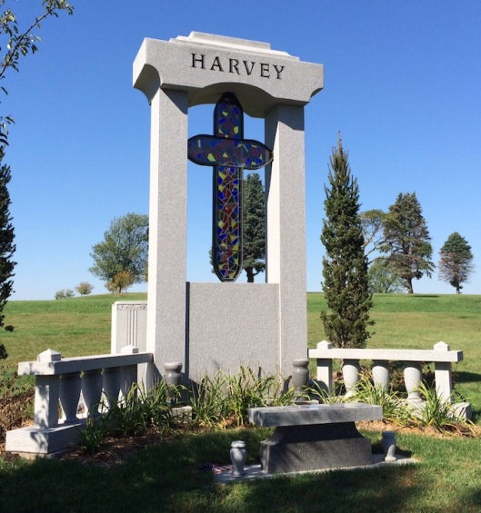 Jack Harvey's monument, featuring a stained glass cross, is a colorful addition to the landscape.