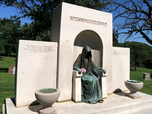 A lone shrouded figure sits awaiting visitors at the Wasserburger gravesites.