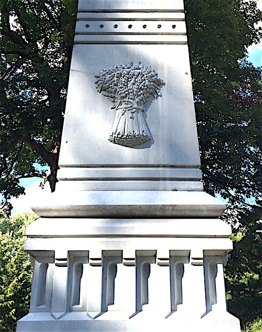 A bound wheat sheaf with a sickle is a common motif on white bronze (zinc) monuments.